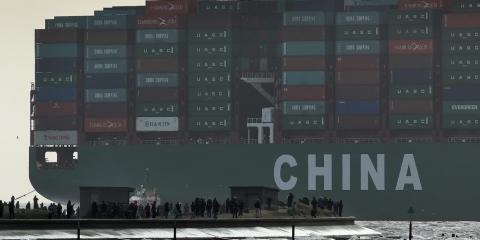 Onlookers watch from a harbor wall as the largest container ship in world, CSCL Globe, docks during its maiden voyage, at the port of Felixstowe in south east England, Jan. 7, 2015.