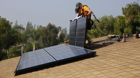 Operarios instalando paneles solares en una casa