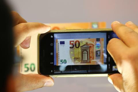 Una persona fotografía un billete de 50 euros.