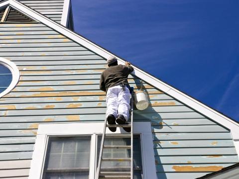 Un pintor trabajando en la fachada de una casa.