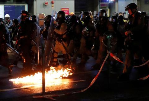 Los policías pasan junto a un cóctel molotov ardiendo.