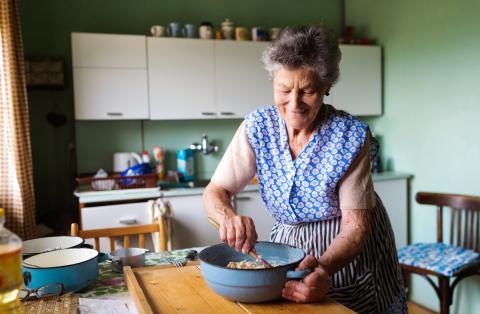 Una señora mayor en la cocina.