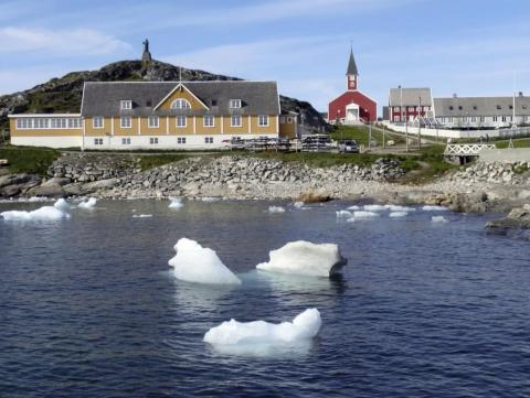 Small pieces of ice float in the water off the shore in Nuuk, Greenland on June 13, 2019.