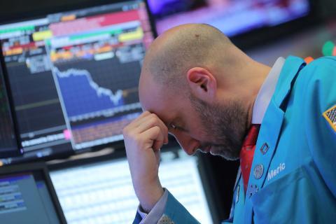 Un trader de Wall Street, con rostro preocupado ante las pantallas de bolsa