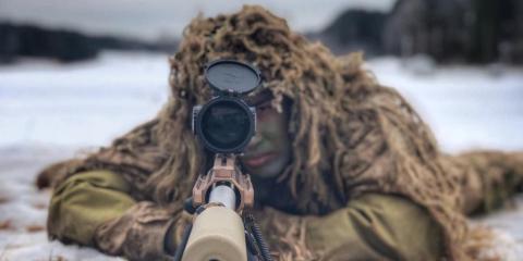 Un Marine mirando a través de un Mk13 Mod 7 en la base de Quantico, en Virginia.
