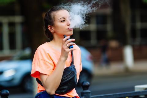 Vapear un cigarro electrónico.