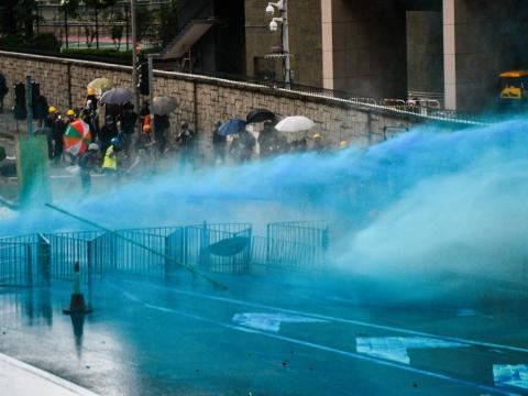 Water cannons coloured with blue dye spray protesters.