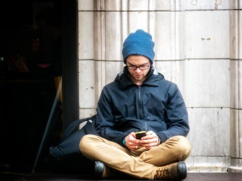 Chico joven sentado mientras usa el móvil