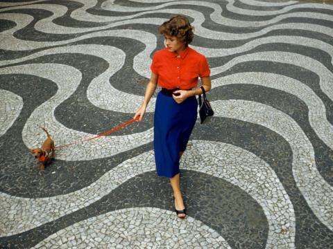 1950s: A woman walks her dachshund along the Copacabana Promenade in Rio de Janeiro, Brazil.