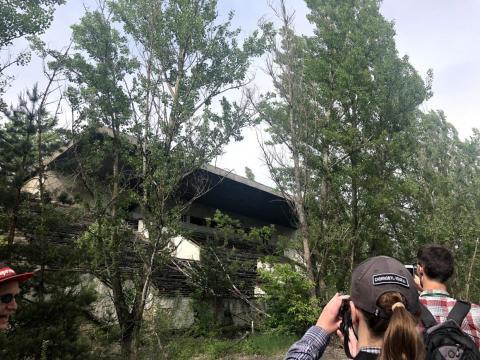 Un edificio abandonado cubierto de follaje dentro de la zona de exclusión.