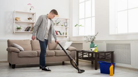 Hombre limpiando la casa con aspiradora