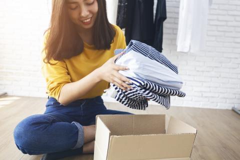 Chica guardando ropa en una caja