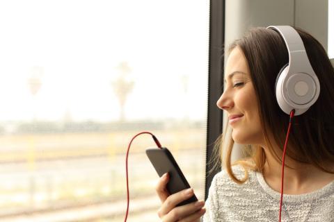 Una mujer escucha música con cascos en un tren