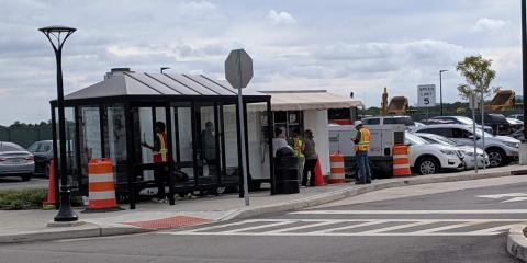 A food truck was serving lunch out in the parking lot, next to a bus stop where workers waited for a ride home.