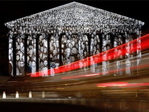 Los coches pasan por la Asamblea Nacional francesa en París, donde se muestra una proyección del artista francés JR, en 2015.