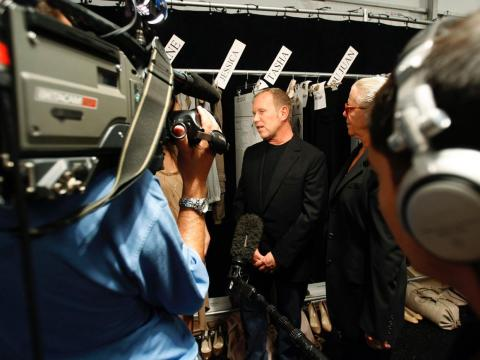Kors da una entrevista durante un desfile de moda.