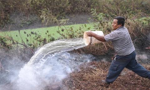 Un hombre apagando un incendio.