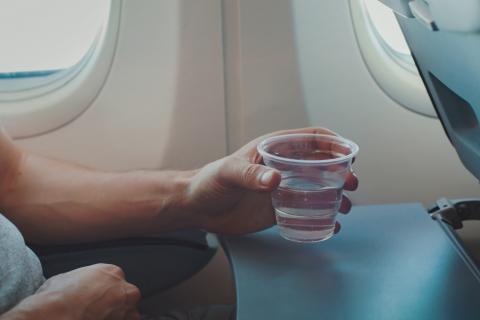Un hombre bebiendo agua en el avión