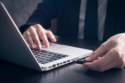 Hombre insertando un USB en el ordenador