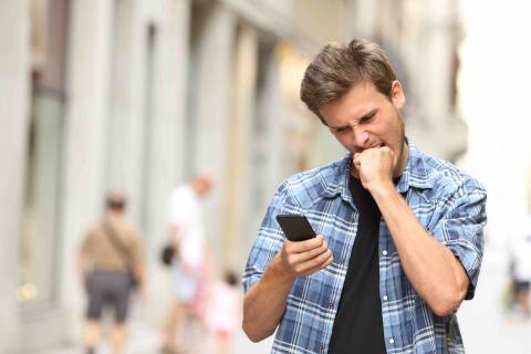 Hombre molesto con un móvil en la mano.
