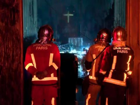 In this image taken from France Televisions video, firefighters stand at an entrance and look at the fire damage inside the Notre Dame cathedral in Paris, Monday April 15, 2019.