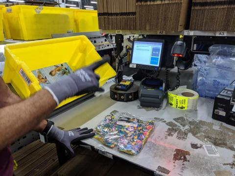 Items come into packing in the signature yellow totes, are scanned, and a bunch of information pops up telling the packer which type of box to use.