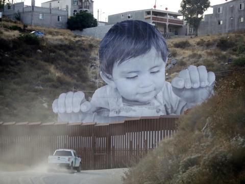Un vehículo de la Patrulla Fronteriza conduce frente al mural de JR en Tecate, México, cerca de Tecate, California, en 2017.