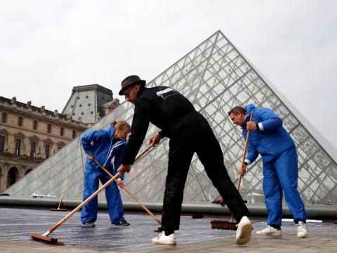 JR trabaja frente al Louvre en 2019.