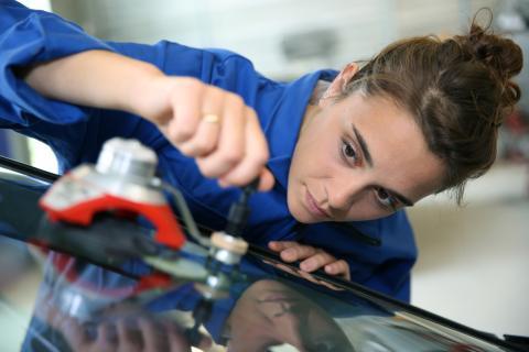 Mujer arreglando la luna de un coche
