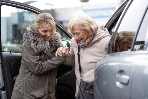 Una mujer ayuda a una persona mayor a salir del coche
