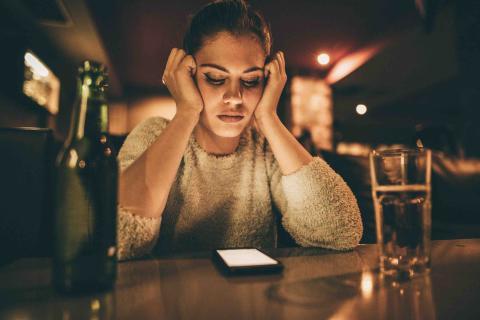 Mujer desesperada viendo el móvil.