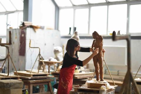 Una mujer disfruta mientras hace una escultura.