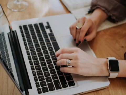 Mujer escribiendo en el ordenador portátil.