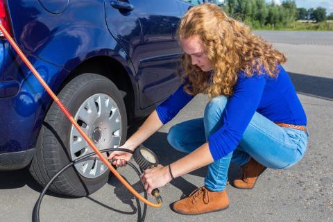 Una mujer infla un neumático del coche