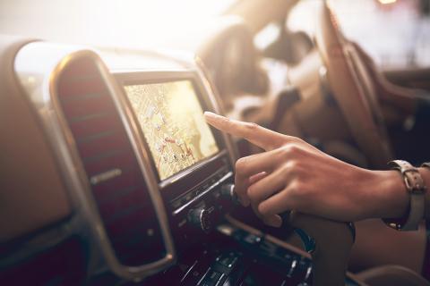 Mujer localizando una ubicación en el mapa de un coche