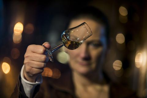Mujer observando una copa de brandy