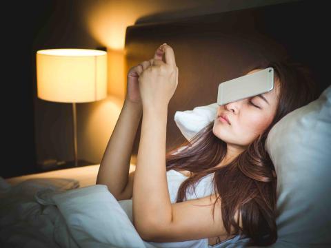 Mujer se queda dormida con móvil en la mano.