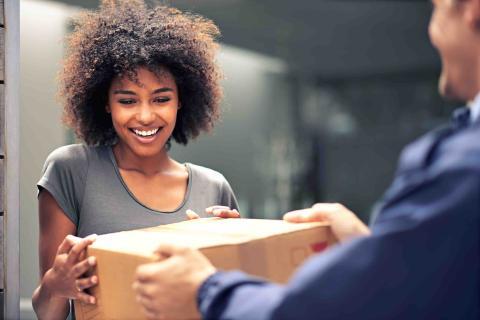 Una mujer recibiendo un paquete.