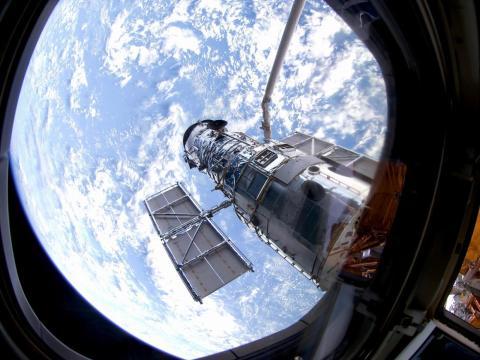 El telescopio Hubble orbitando alrededor de la Tierra.