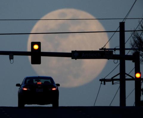 En esta foto del 30 de marzo de 2018, un automovilista espera en un semáforo mientras la luna llena se eleva en Overland Park, Kansas.