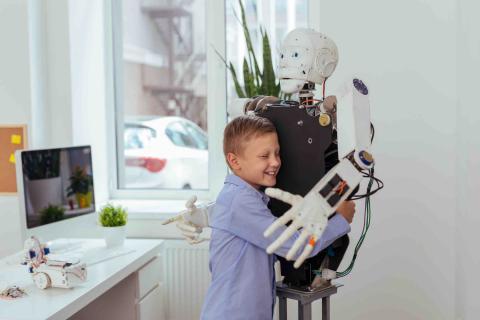 Un niño abraza a un robot.