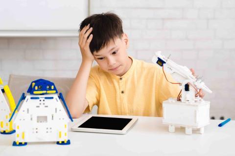 Un niño confuso frente a un robot.