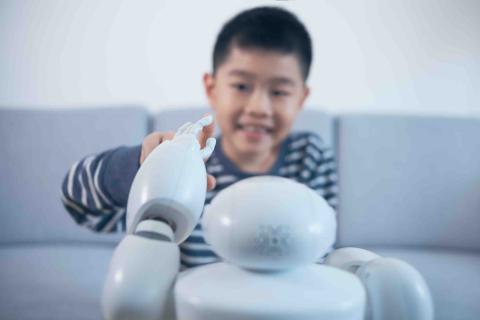 Un niño interactúa con un robot.