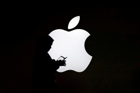 Una persona pasa por delante del logotipo de Apple
