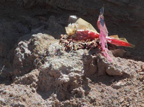 A portion of the site where a vehicle crashed near Roswell, New Mexico in 1947 is marked with flowers and two small flags.