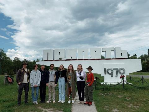 Czub y compañeros de viaje frente a un cartel en Pripyat.