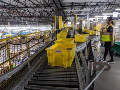 """These yellow plastic bins are called """"totes"""" in the fulfillment center — everything that comes in or out of this warehouse must fit within one of these. There are more than 40,000 such bins in this facility alone."""