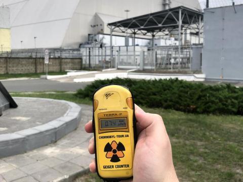 Zwick sosteniendo un contador Geiger frente al reactor dañado en la zona de exclusión.