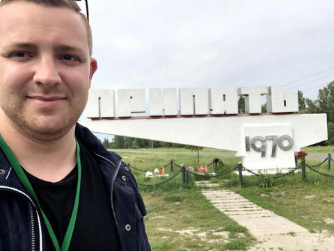 """Zwick delante de un cartel que dice """"Pripyat"""" en ruso."""