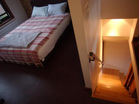 Un dormitorio elevado en una pequeña casa.